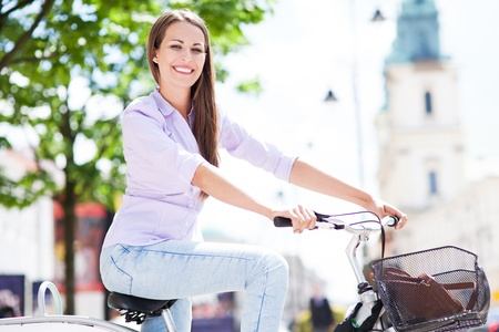 girl on bike: Woman riding a bike in the city