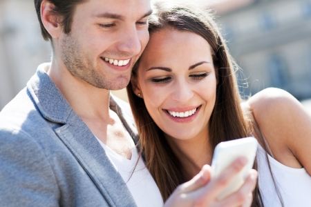 Smiling couple with mobile phone photo