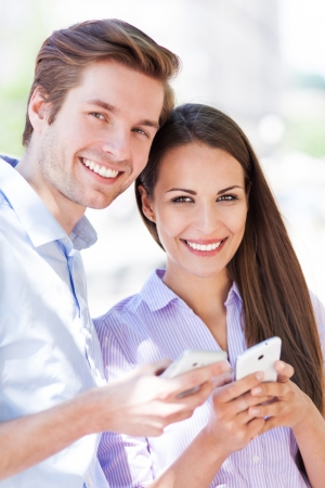Smiling couple with mobile phones photo