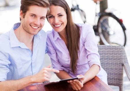 persona feliz: Pareja con tableta digital al aire libre