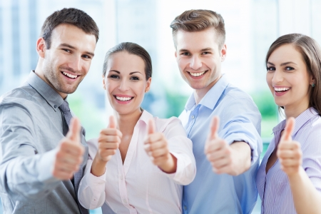 exito: Equipo de negocios con los pulgares para arriba