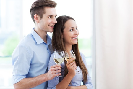Couple drinking wine in modern apartment photo