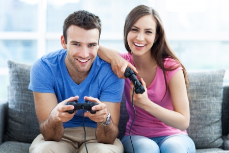 Couple on sofa playing video games photo