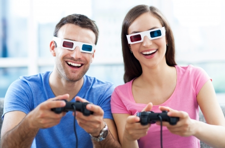 playing a game: Couple in 3d glasses playing video games