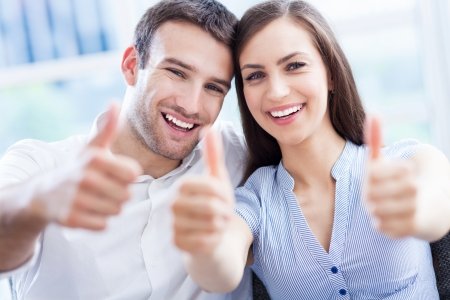 two thumbs up: Young couple with thumbs up