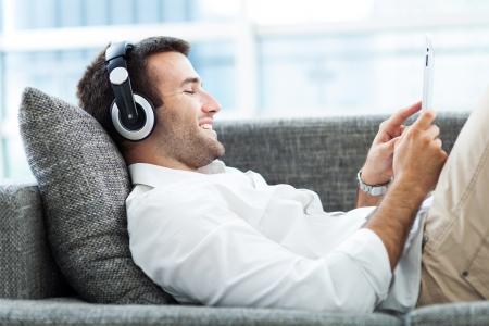 escuchando musica: Hombre en el sofá con los auriculares y la tableta digital