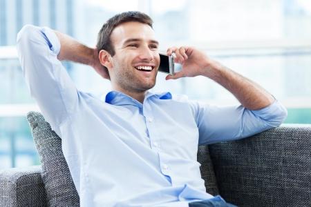 uomo felice: L'uomo sul divano con il cellulare Archivio Fotografico