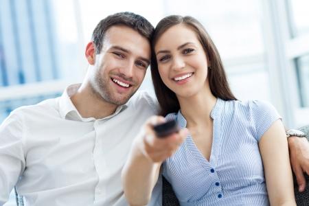 pareja viendo television: Pareja joven con el telecontrol de la TV