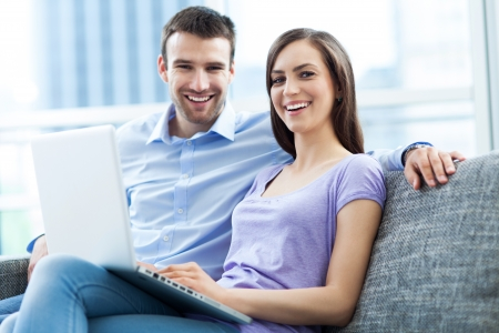 woman sitting with laptop: Couple on sofa with laptop Stock Photo