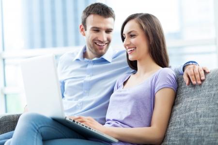 Couple on sofa with laptop photo