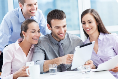 four people: Coworkers looking at digital tablet Stock Photo