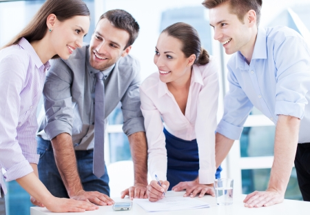 corporate meeting: Coworkers leaning over table in office