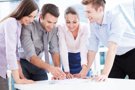 jornada de trabajo: Compañeros de trabajo que se inclinan sobre la mesa en el cargo