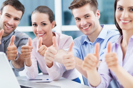 Young business people showing thumbs up photo