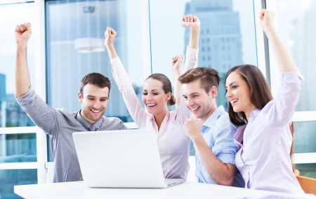 Business people cheering at laptop photo