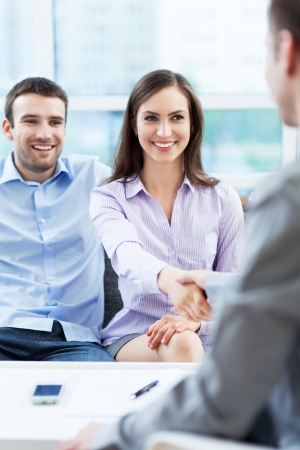 loaning: Couple shaking hands to real-estate agent at home