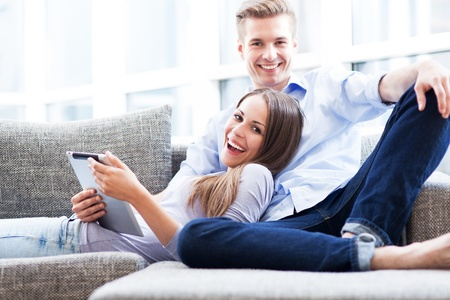 modern sofa: Couple on sofa with digital tablet Stock Photo
