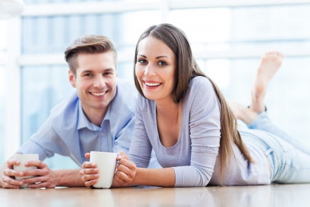 hombre tomando cafe: Pareja en el suelo bebiendo café