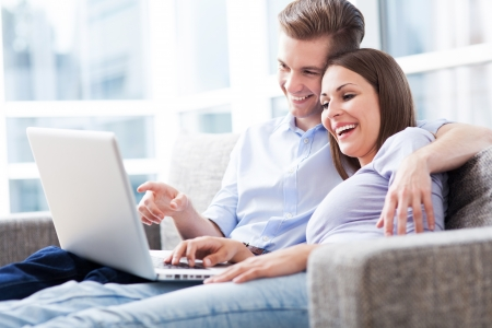 couple couch: Couple on sofa with laptop Stock Photo