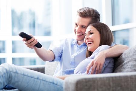 personas mirando: Pareja en el sofá con el control remoto del televisor Foto de archivo