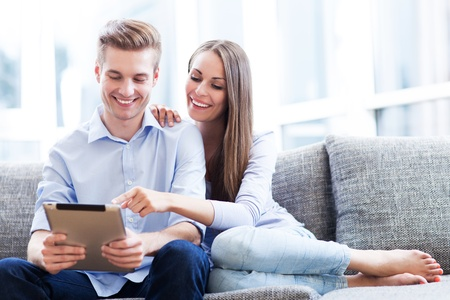 modern sofa: Couple using digital tablet Stock Photo