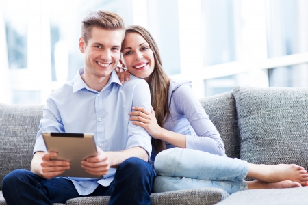 Couple on sofa with digital tablet Stock Photo - 20670231