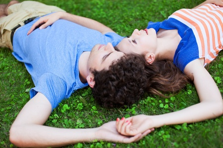 lying on grass: Young couple lying on grass