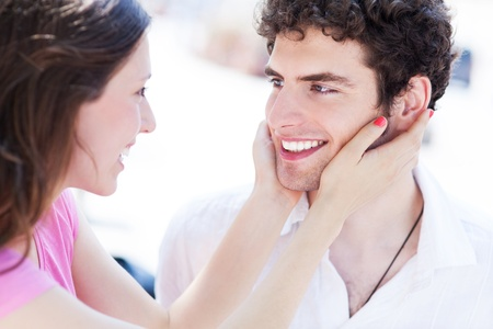 toothy smile: Woman holding man s face in her hands