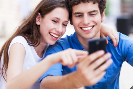 pareja adolescente: Pareja joven mirando el tel�fono m�vil Foto de archivo