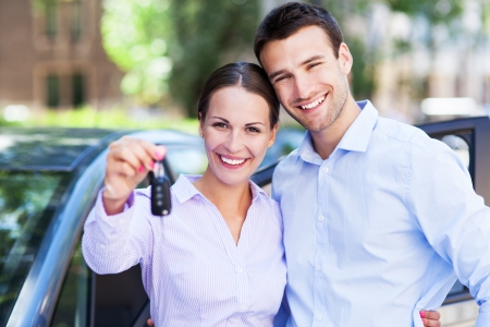 car dealers: Young couple with keys to new car