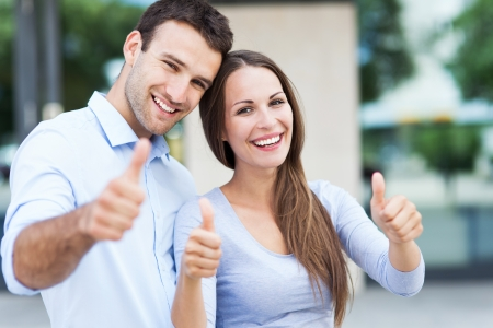 thumbs up: Smiling couple with thumbs up Stock Photo