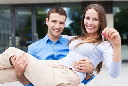Man carrying woman into new house Stock Photo