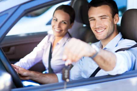 conducci�n: Pareja joven con claves del nuevo coche Foto de archivo