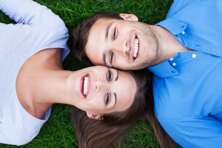 lying on grass: Happy couple lying on grass