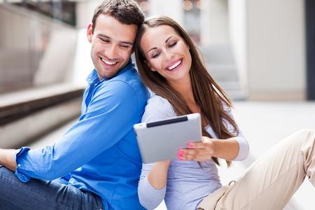 Couple using digital tablet outdoors photo