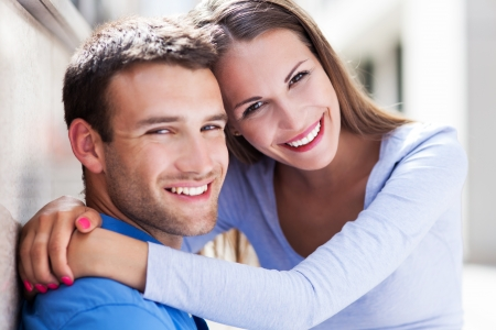 young man smiling: Young couple hugging