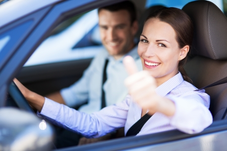 Couple sitting in car with thumbs up photo