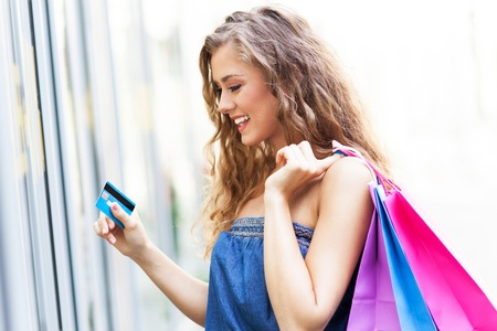 Woman with credit card and shopping bags photo