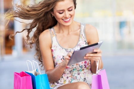 Shopping woman using digital tablet photo