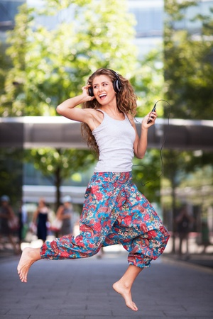 barefoot teens: Young urban woman jumping Stock Photo