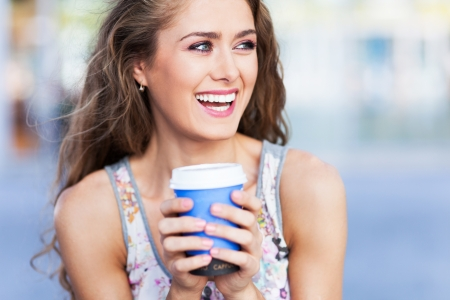 women holding cup: Young coffee drinker Stock Photo