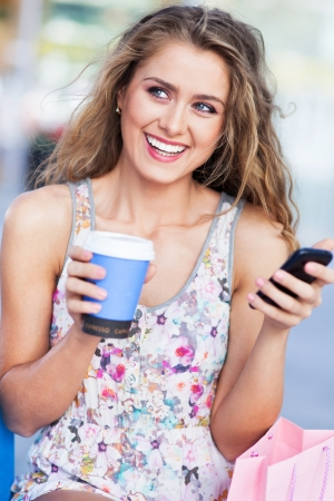 Woman with coffee and mobile phone photo