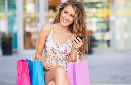 mobile shopping: Woman having a break from shopping