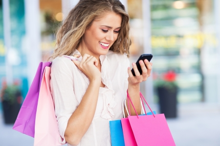 Shopping woman with mobile phone Imagens