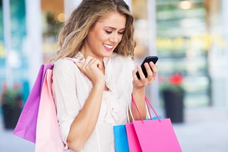 Winkelen vrouw met mobiele telefoon Stockfoto