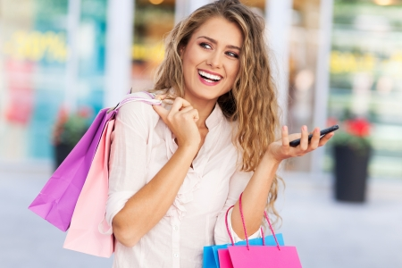 sms: Shopping woman with mobile phone Stock Photo