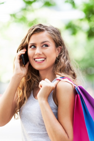Woman talking on mobile phone and holding shopping bags Stock Photo - 21620881