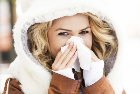 sick day: Woman blowing her nose Stock Photo