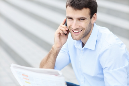 businessman smiling: Man with newspaper and mobile phone