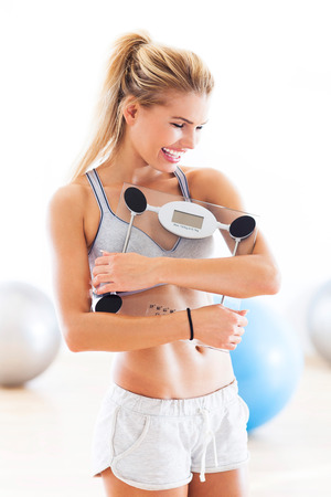 woman on scale: Woman holding weight scale Stock Photo